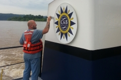 A C&B associate painting part of a boat