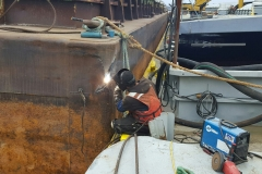 A C&B associate performing topside repair on a barge