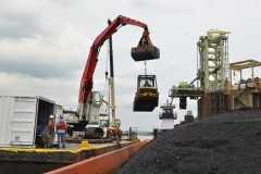 C&B using its excavator to lower a skid steer into a coal barge for unloading
